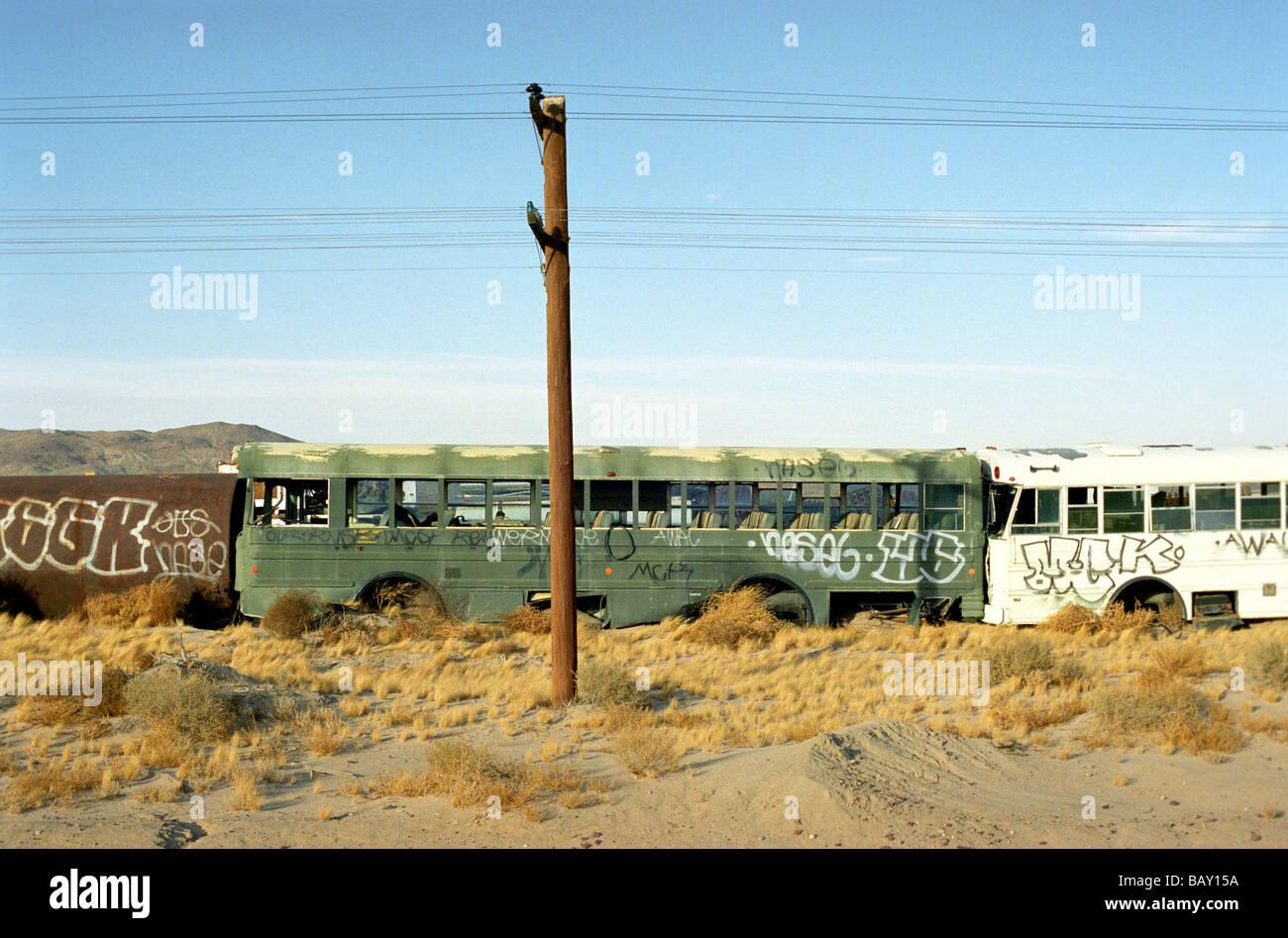 Old buses on a scrap yard, Mojave Desert, California, USA - Stock Image