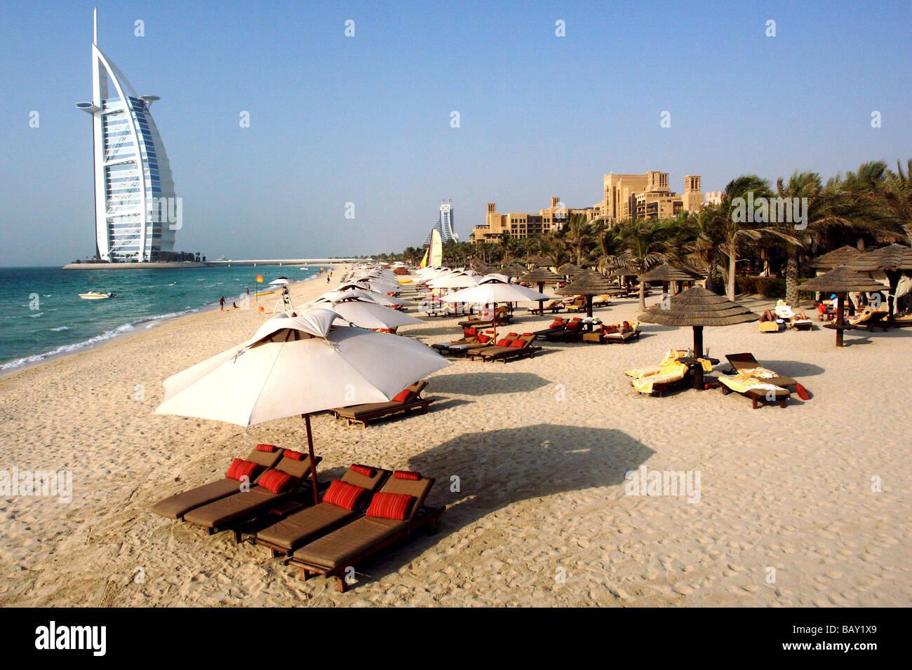 Sun Loungers at Jumeirah Beach, View at Burj al Arab Hotel, Jumeirah District, Dubai, United Arab Emirates, UAE - Stock Image