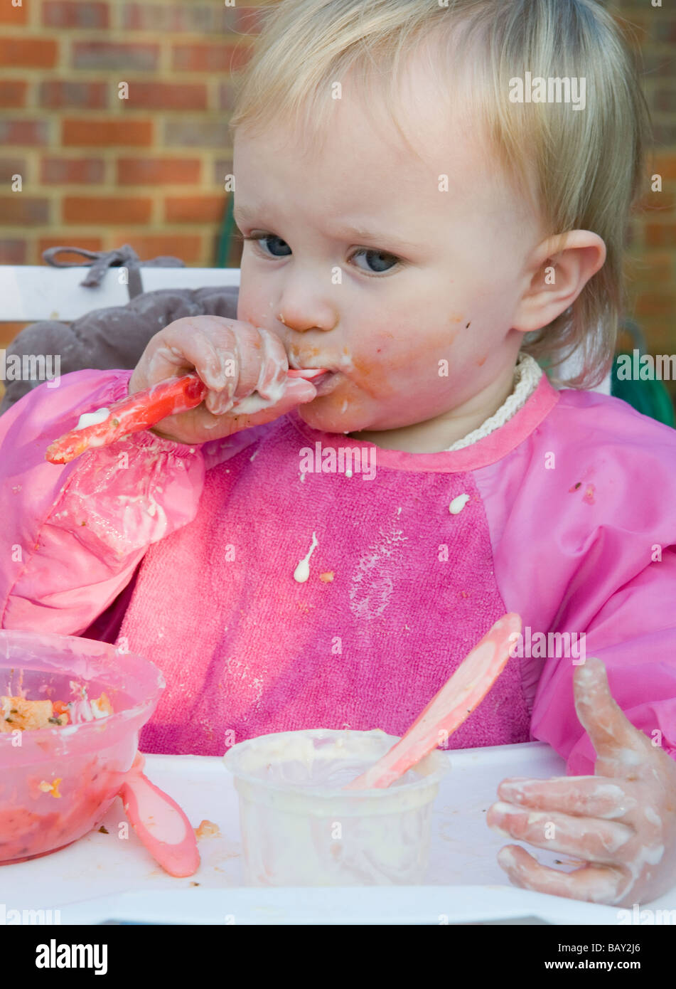 Toddler, 16months old,  girl , feeding herself and causing a mess - Stock Image