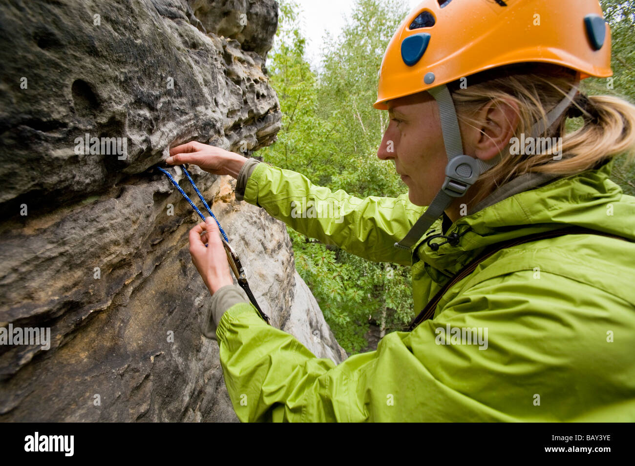 A young woman attaching a loop, sling, Alter Weg route, Wegelagerer Rocks, Bielatal, Elbe Sandstone Mountains, Saxon - Stock Image