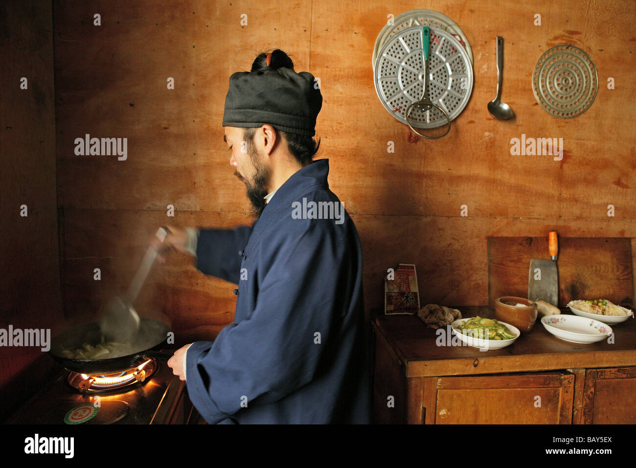 A monk cooking in the kitchen of the monastery Cui Yun Gong, Hua Shan, Shaanxi province, China, Asia - Stock Image
