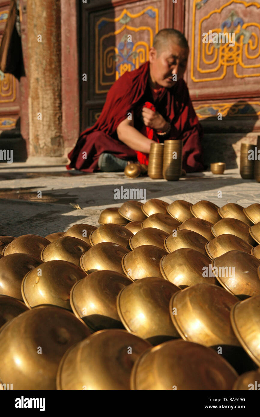 Monk filling the butter lamps in readiness for the birthday celebrations of Wenshu, Shuxiang temple, Mount Wutai, - Stock Image