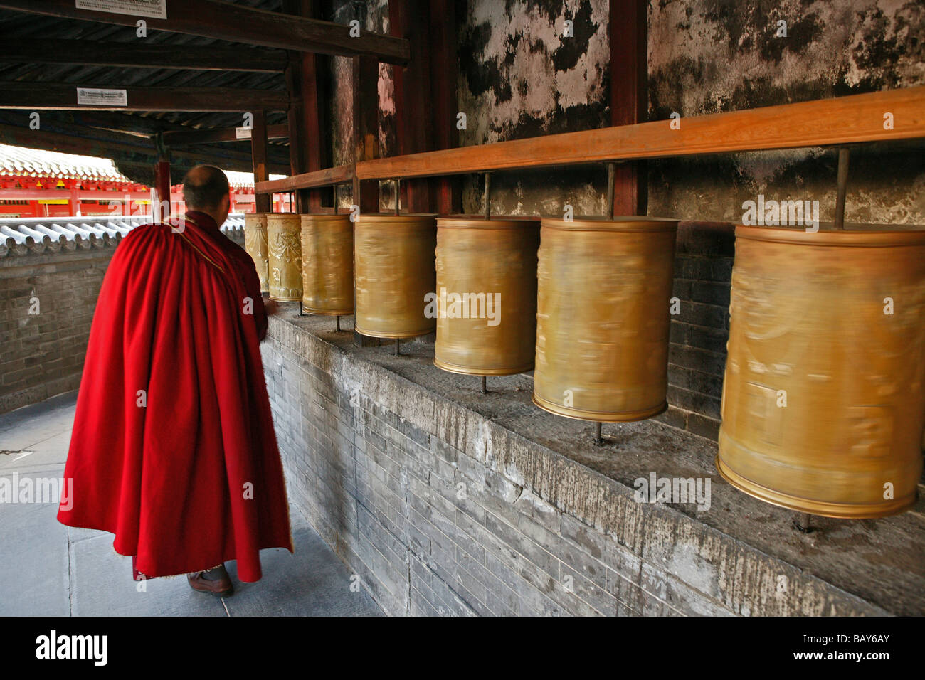 Lama monk turns the prayer wheels at the base of the Great White Pagoda, during the birthday celebrations for Wenshu, - Stock Image