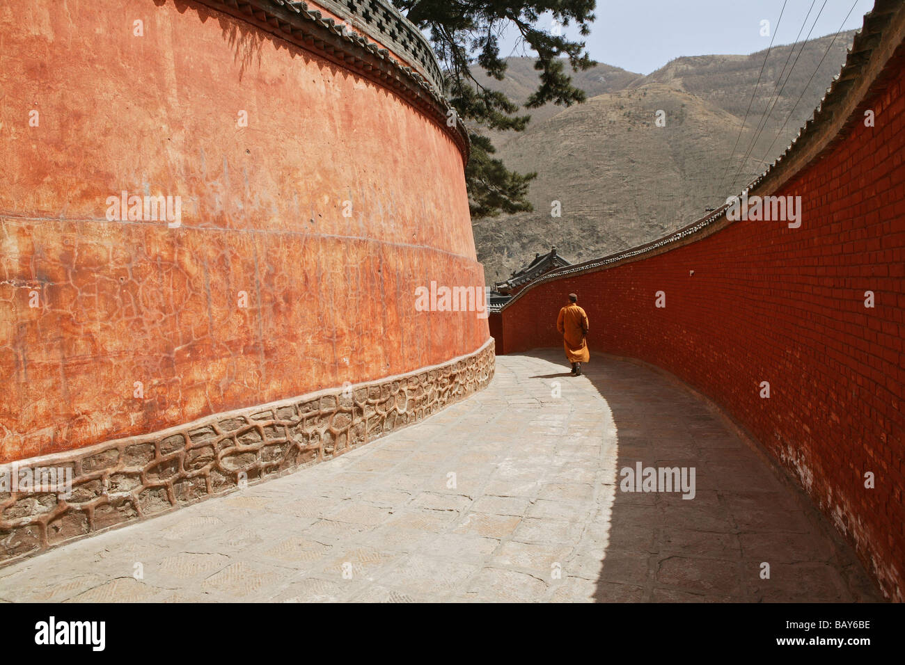 Monk walking to Pusa Ding Summit, high walls of the monastery, Xiantong Monastery, Wutai Shan, Five Terrace Mountain, - Stock Image