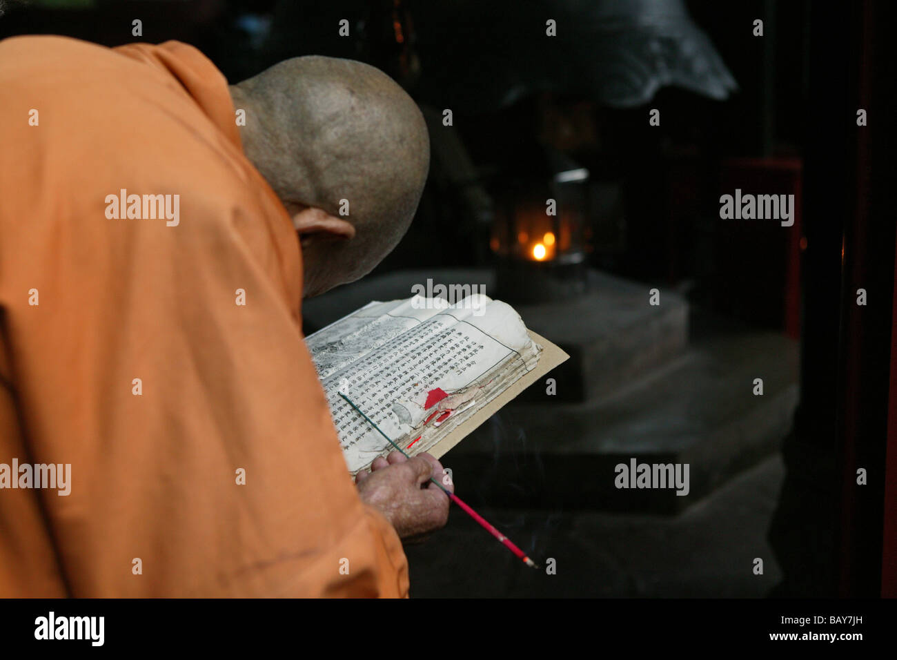 Old monk reading holy scripts, Wannian monastery, Emei Shan, Sichuan province, China, Asia - Stock Image