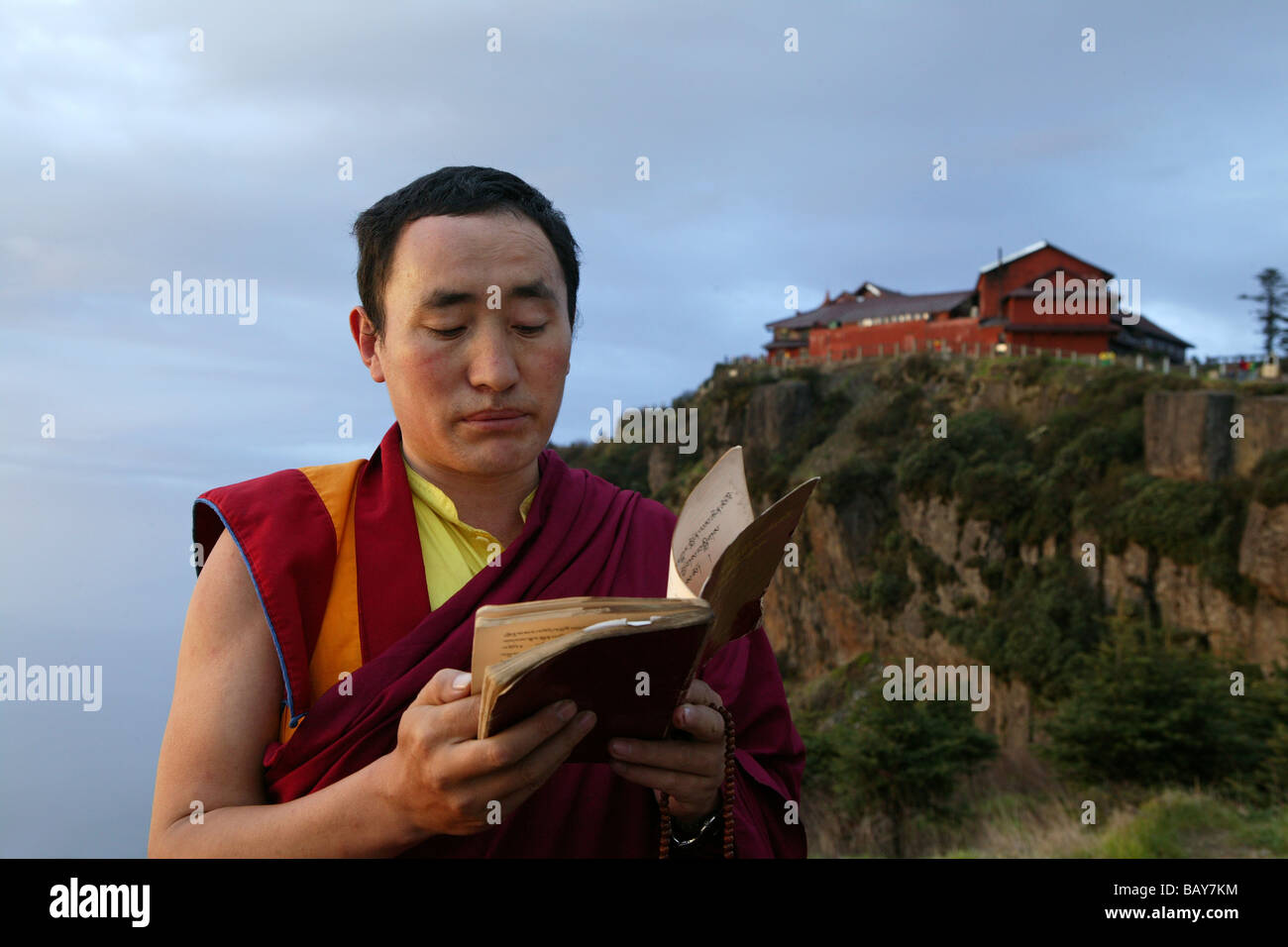 Tibetan monk reading holy scripts at sunrise, Emei Shan mountains, Sichuan province, China, Asia - Stock Image