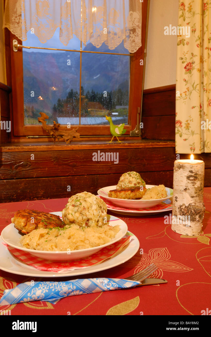 laid table with two portions of Tyrolean Kaspressknoedel and Speckknoedel with sauerkraut, Tyrol, Austria - Stock Image