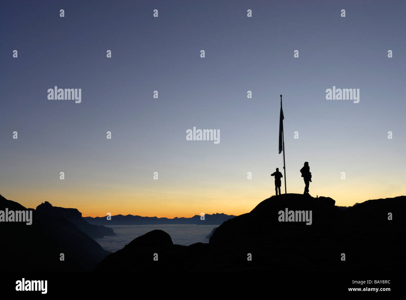 two hikers on dome with flagpole, dawn above fog bank in valley Gschnitztal, Kirchdachspitze in background, Bremer - Stock Image