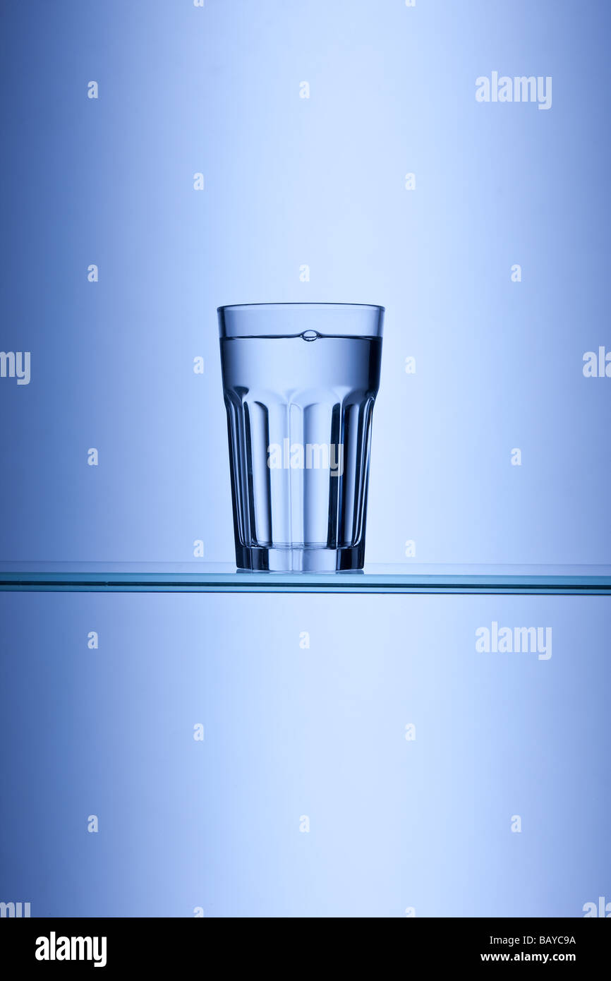 glass of drinking water on blue background Stock Photo