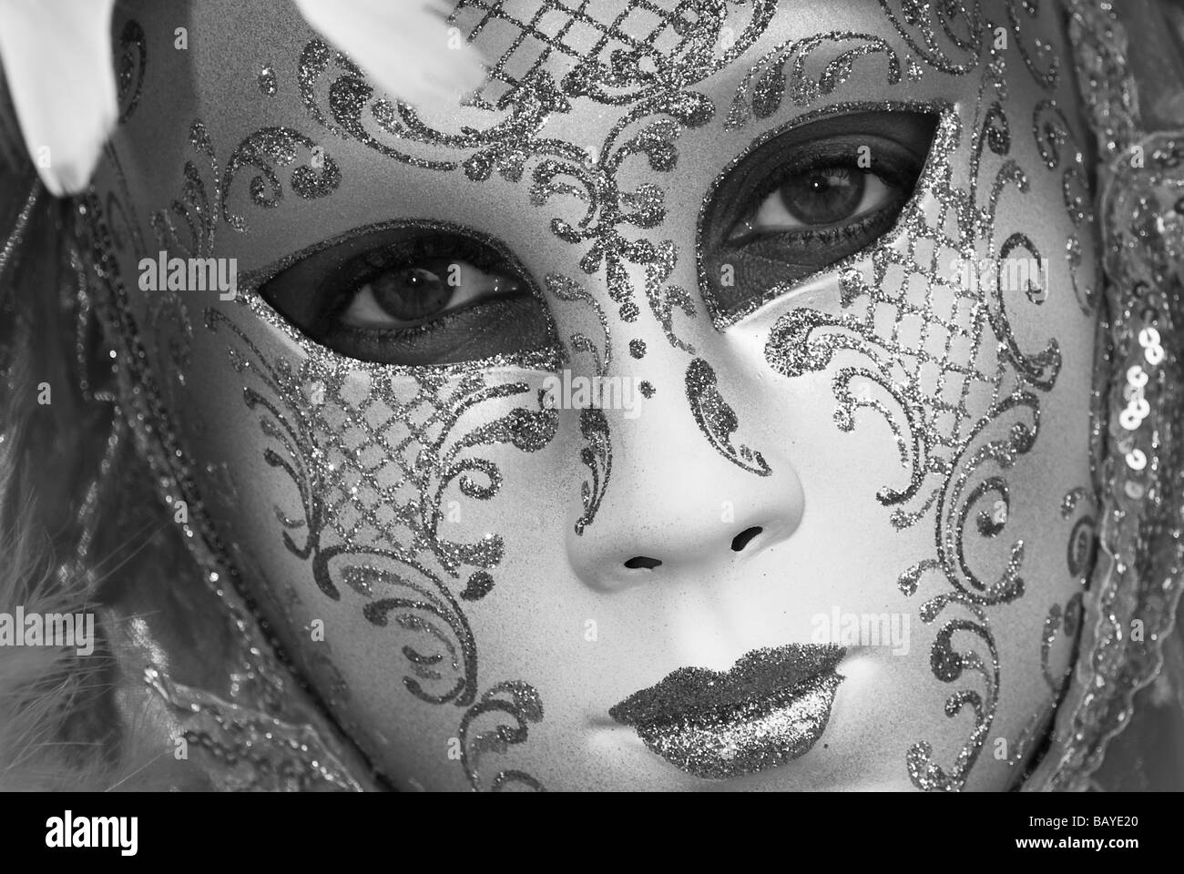 Black and white close up of girl with a venetian carnival mask - Stock Image