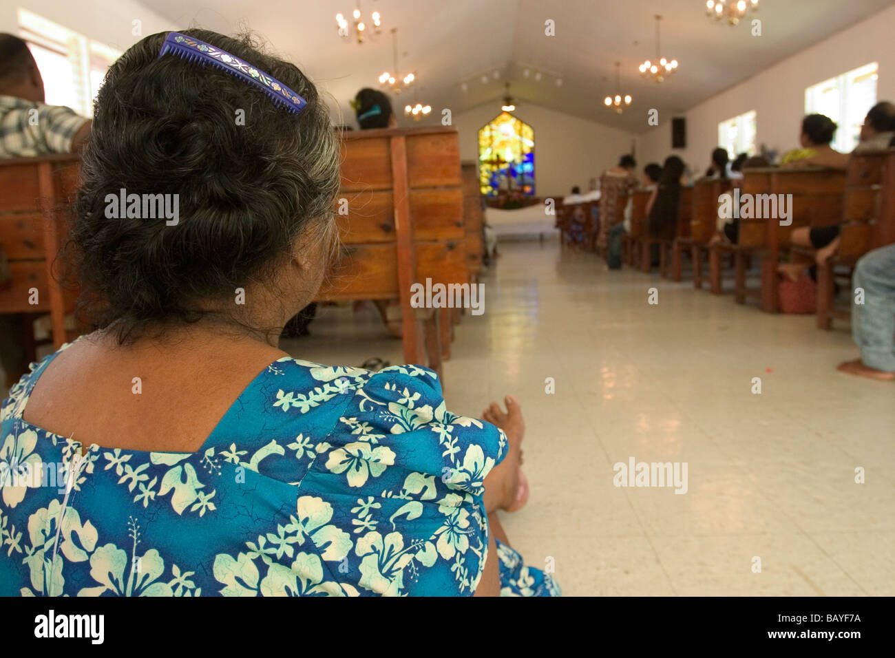 A Micronesian woman sits at the back of a church sanctuary in Kolonia Town, Pohnpei Island, Federated States of - Stock Image