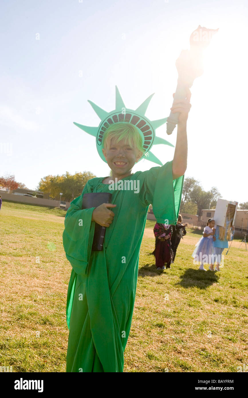 elementary school age girl dressed up in Statue of Liberty halloween costume, holding torch to sunlight - Stock Image