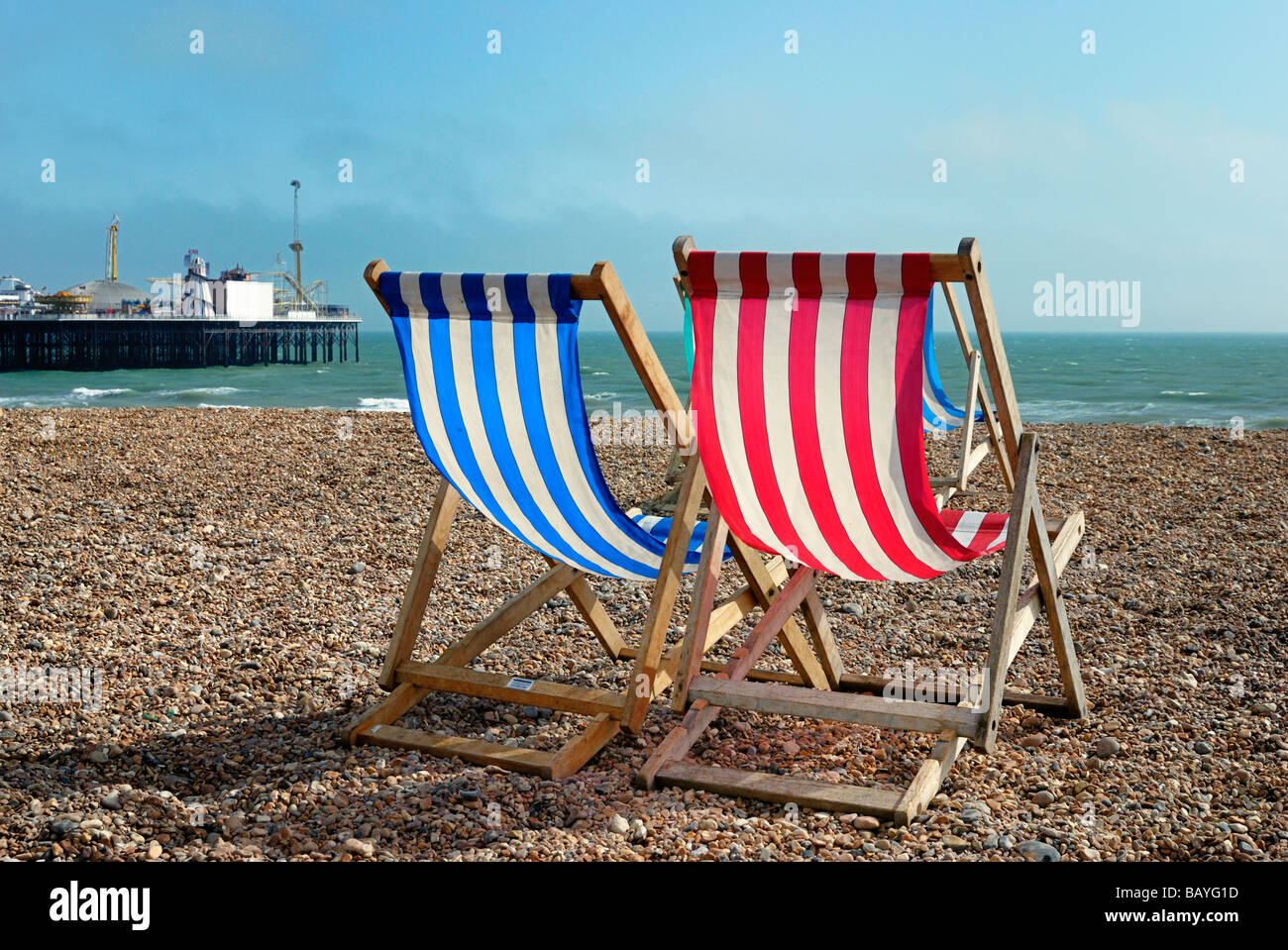 Two deckchairs on beach with Brighton Pier in background Stock Photo