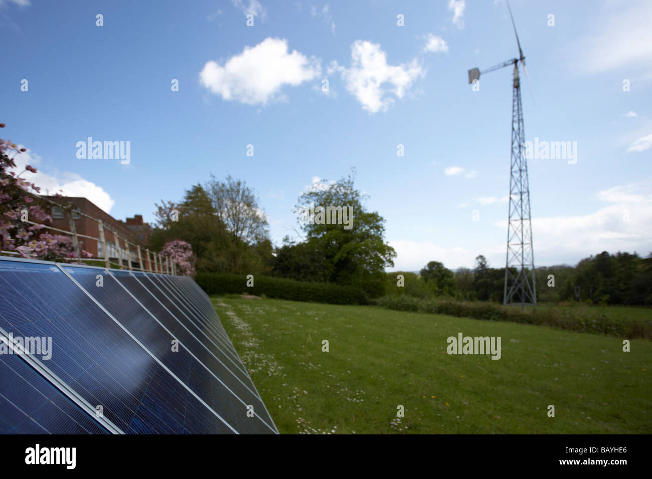 sun shining down on an array of blue tinted polycrystalline silicon photovoltaic solar panels and medium sized wind - Stock Image