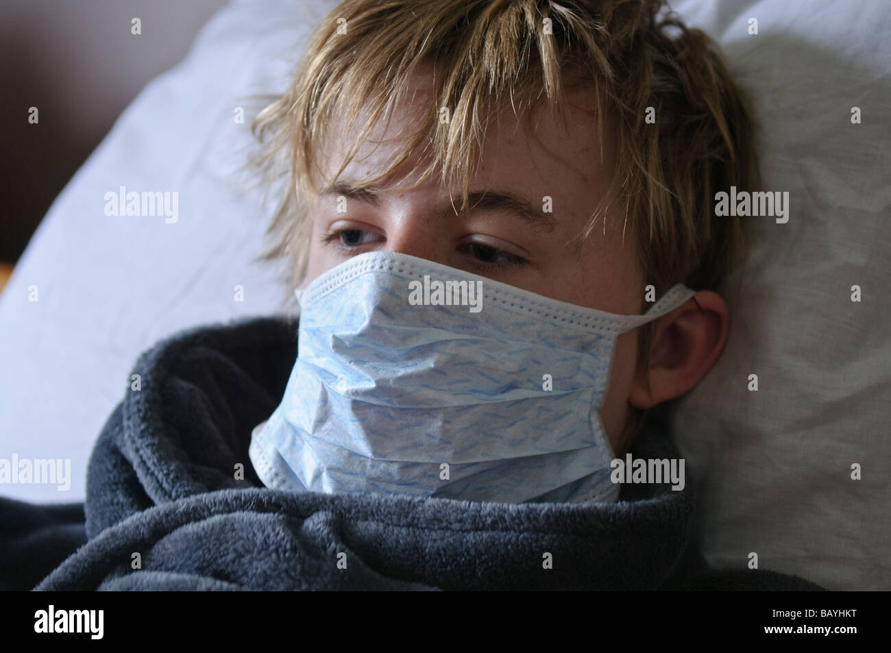 Teenage boy lying in bed wearing a mask - Stock Image