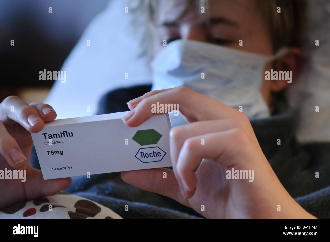 Teenage boy reads back of Tamiflu box while lying in bed wearing a mask - Stock Image