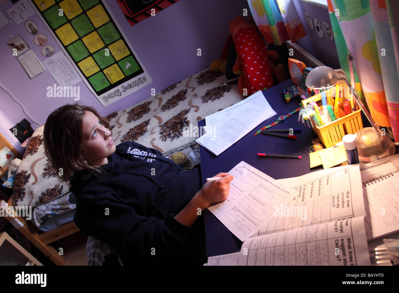 Young teenage girl aged 15 years old thinking doing her homework school study in her bedroom at home - Stock Image