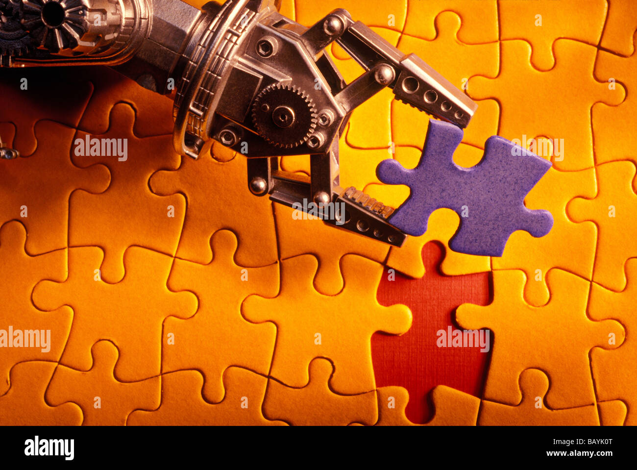 Robot arm holding jigsaw puzzle piece - Stock Image