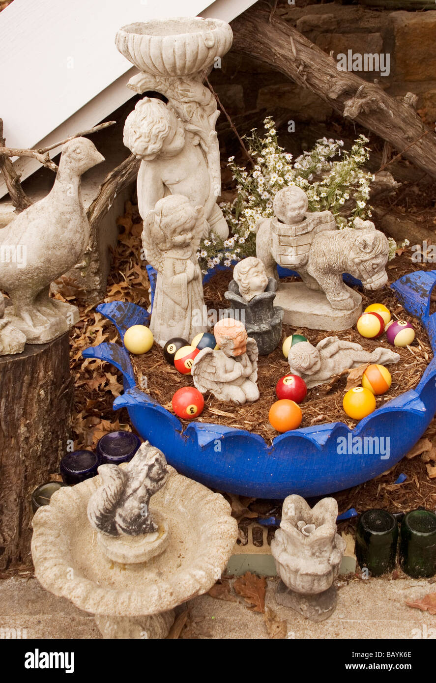 Tacky cement statuary and colorful pool balls decorate the corner of a homeowner's yard. - Stock Image