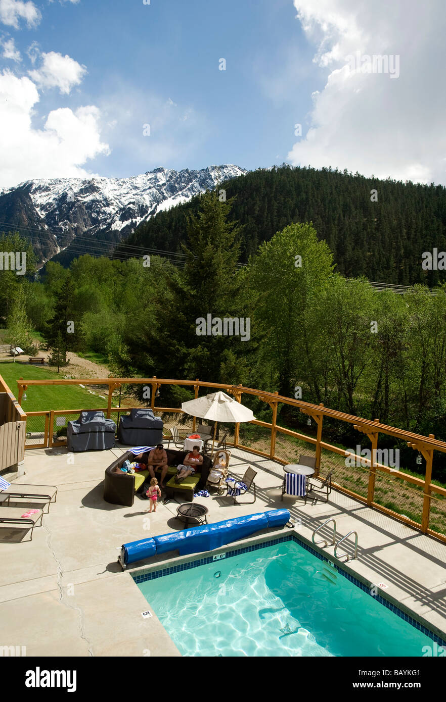 Hotel guests enjoy the sun pool side with Mt Currie in the background Pemberton BC Canada - Stock Image