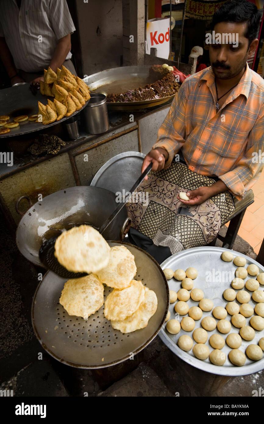 Indian man frying puri / poori bread in Shimla. Himachal Pradesh. India. - Stock Image