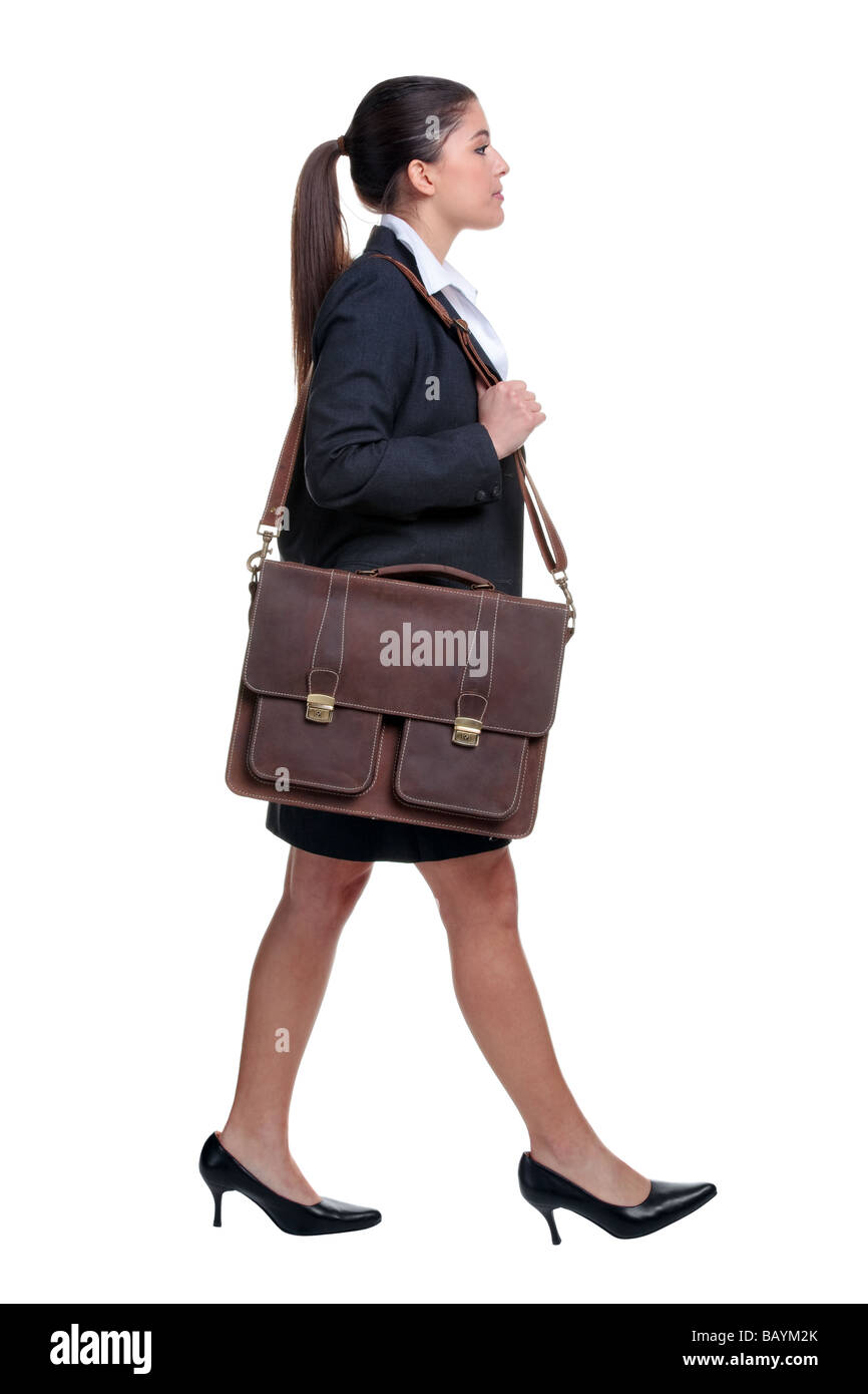 Businesswoman walking with briefcase over her shoulder isolated on white background - Stock Image