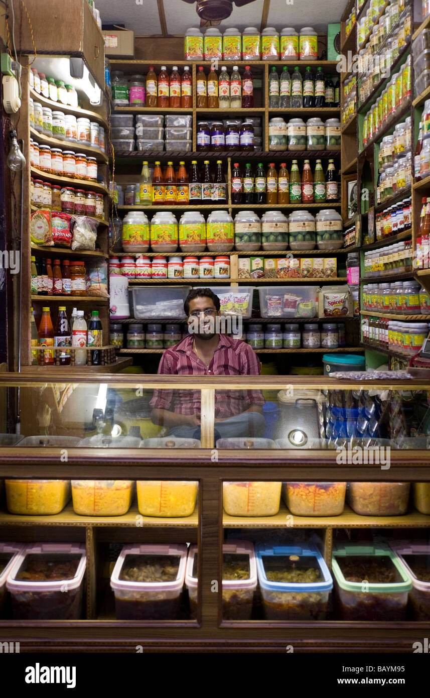 Small shop selling food and drinks, and the shop keeper, in Shimla. Himachal Pradesh. India. - Stock Image
