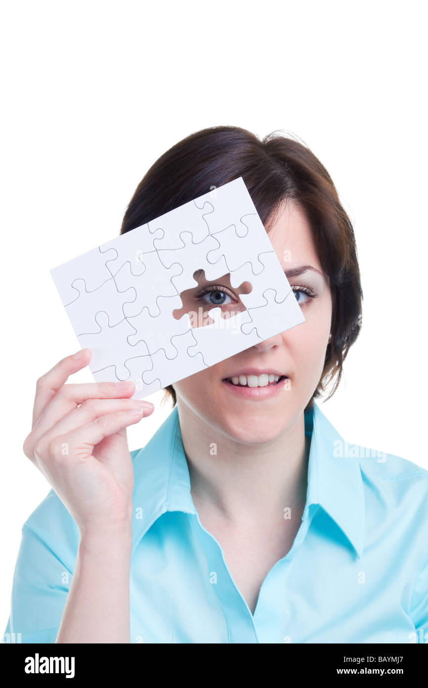 Woman looking through the missing piece of a jigsaw puzzle isolated on white background - Stock Image