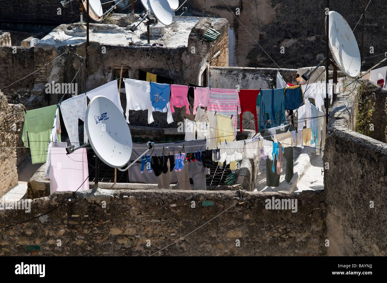 Over the rooftops view of Fes. Showing satellite dishes rows of washing hung out, derelict Riads, grass growing - Stock Image