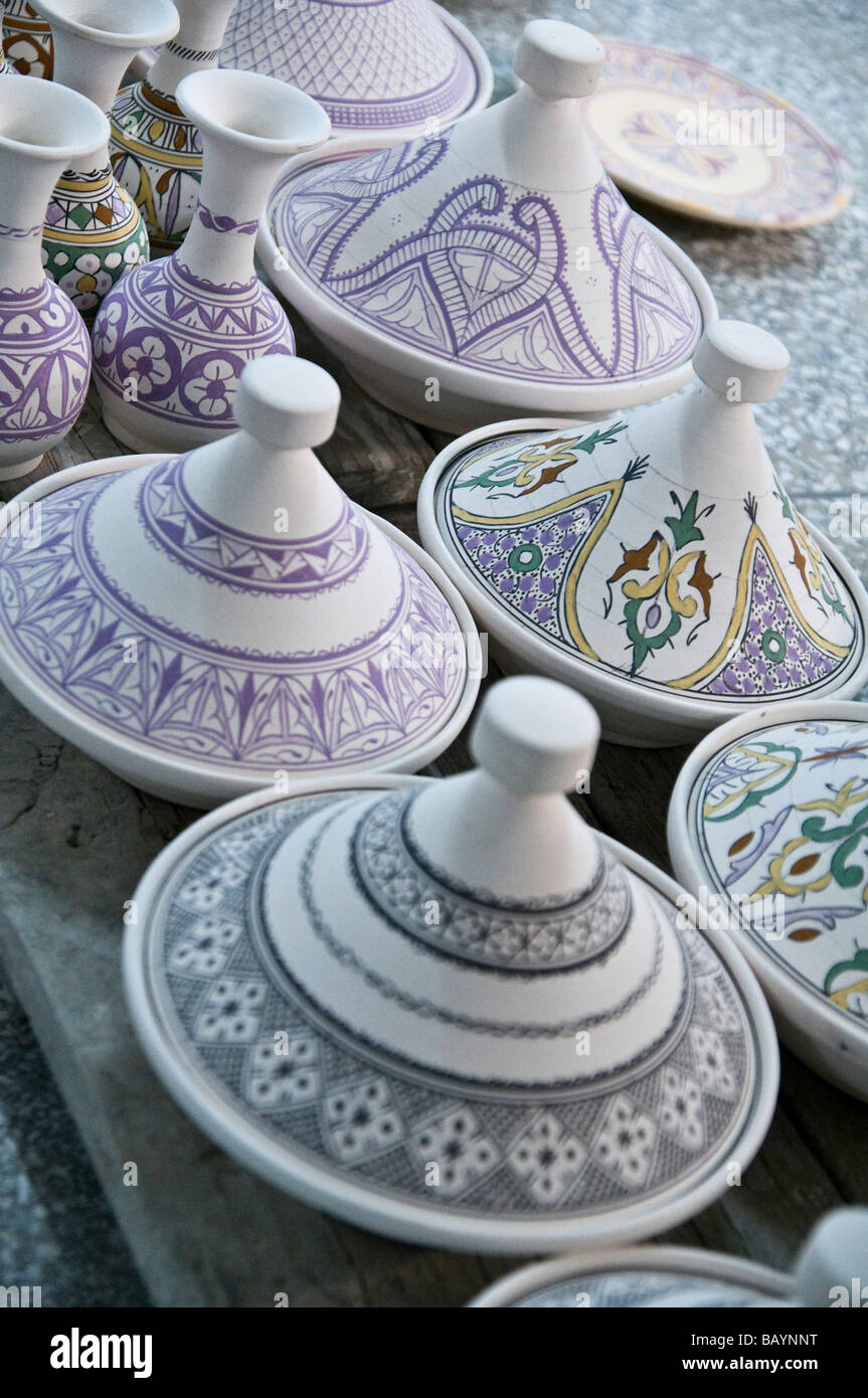 A row of hand painted earthenware tagines, plates and vases at the bisque stage - Stock Image