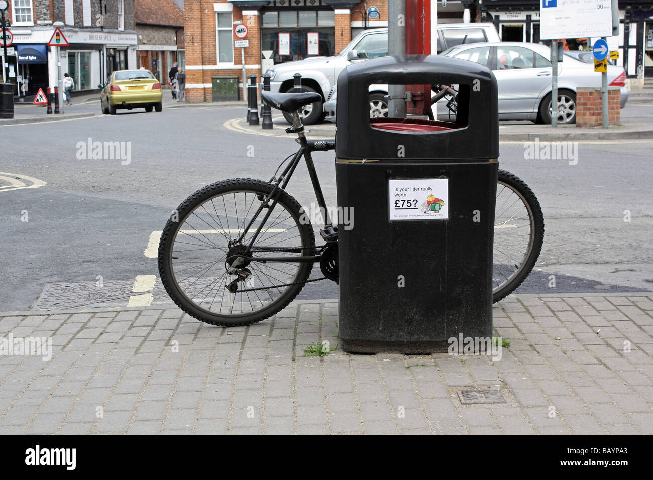 bicycle left next to a litter bin - Stock Image