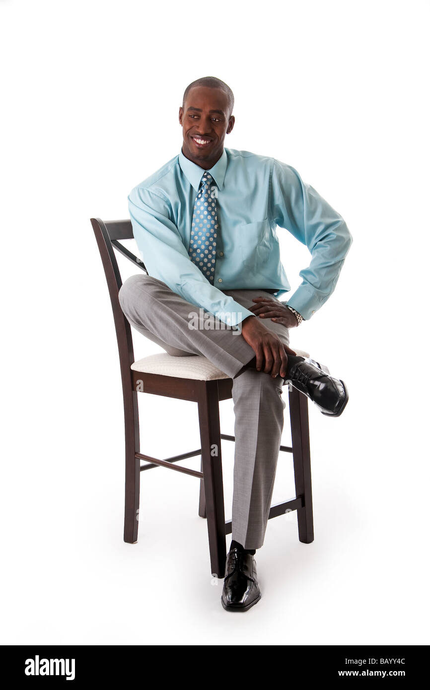 Handsome African American business man smiling sitting on chair wearing sea green shirt and gray pants isolated  sc 1 st  Alamy & Handsome African American business man smiling sitting on chair ...