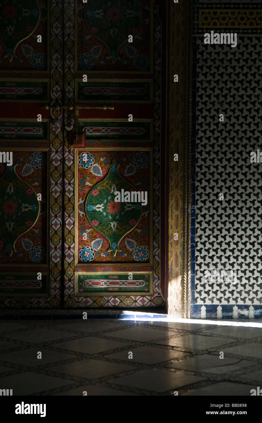 Shaft of sunlight on beautiful painted ornate doors and mosaic walls at Riad Mokri - now a music school. - Stock Image