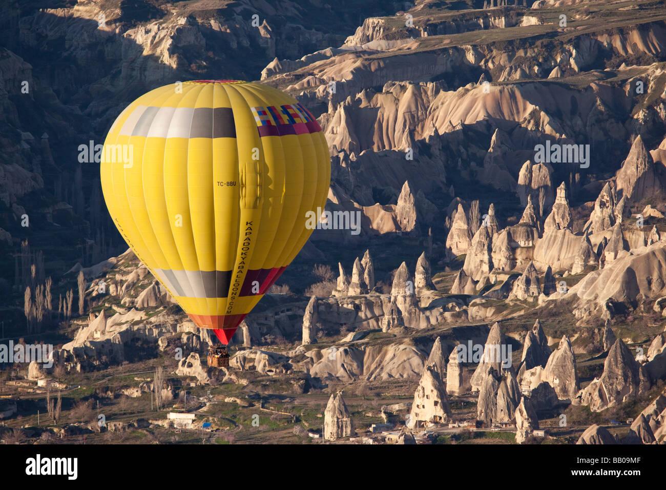Hot air balloon over the rugged terrain of Cappadocia Turkey - Stock Image