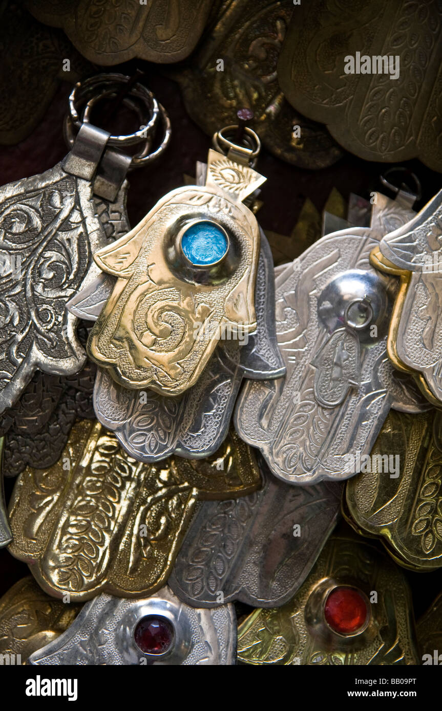Dozens of Khamsa - or Fatima's hands. Hanging for sale at market stall in the medina, Fes, Morocco - Stock Image