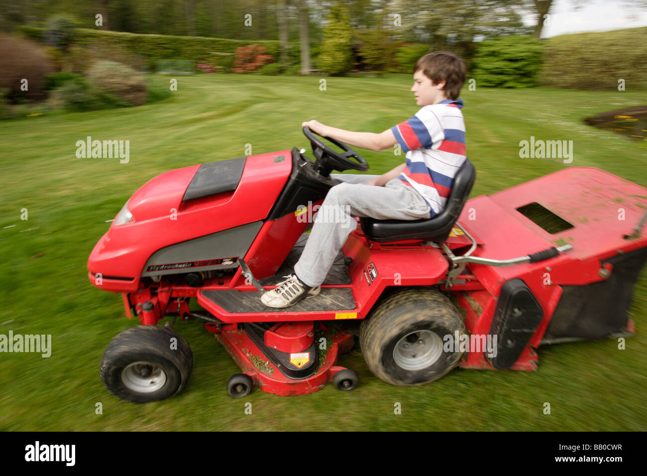 A boy doing the lawn mowing - Stock Image