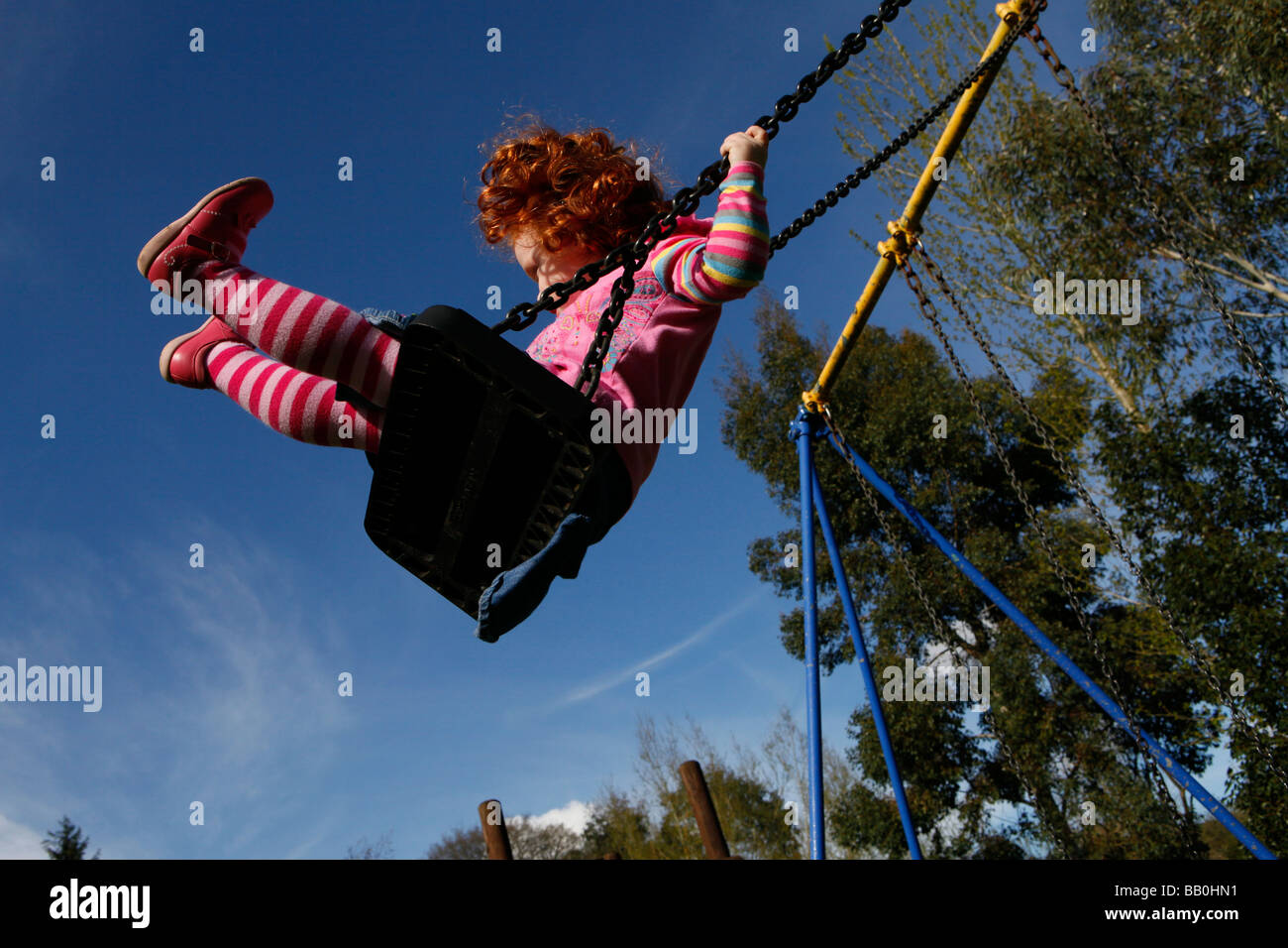 Three year old girl with red hair playing on the swings in the park in the sunshine. - Stock Image
