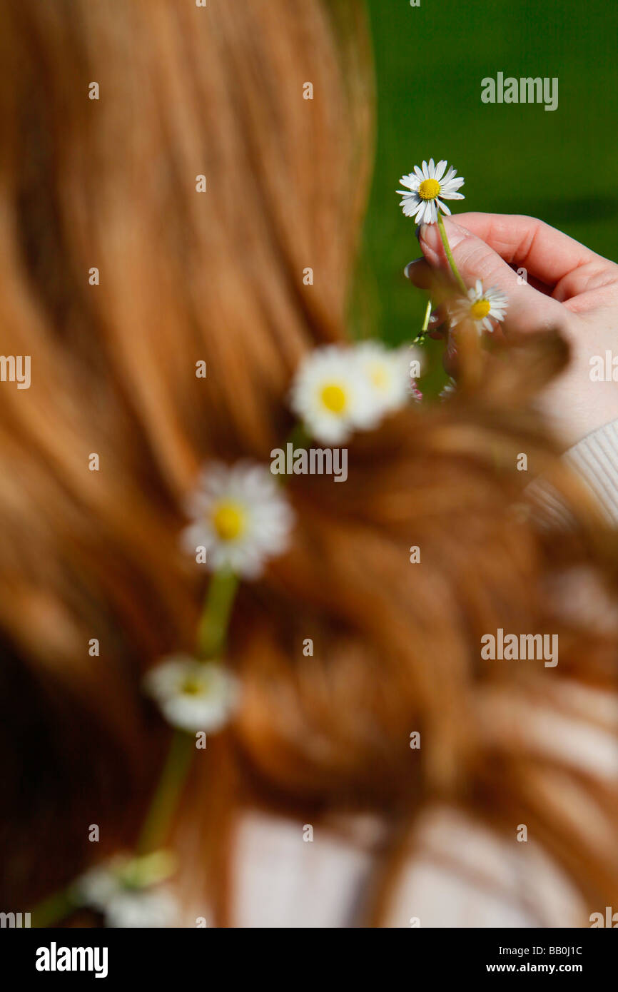 woman holding a daisy chain in the sunshine. - Stock Image