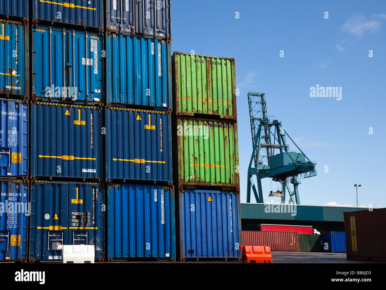 Crane and containers on a dockside ready for loading onto a container ship, Greenock, Scotland - Stock Image