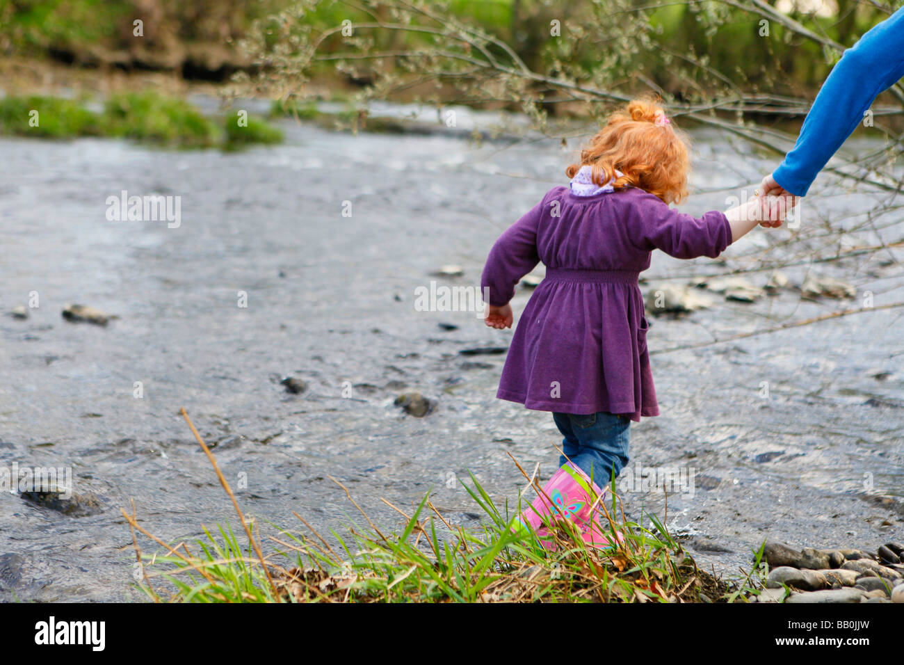 Little girl paddling in the river with red curly hair. - Stock Image