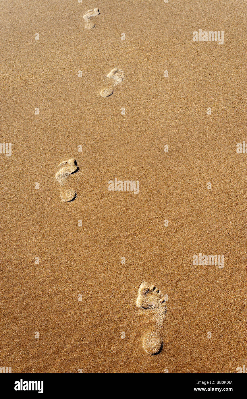 Woman's footprints in sand - Stock Image