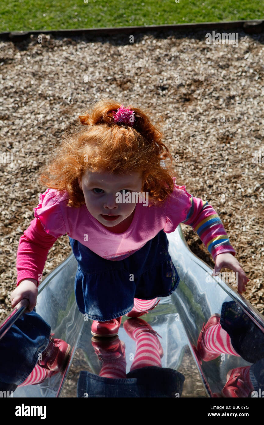 Little girl with red hair climbing up the slide at the park . - Stock Image