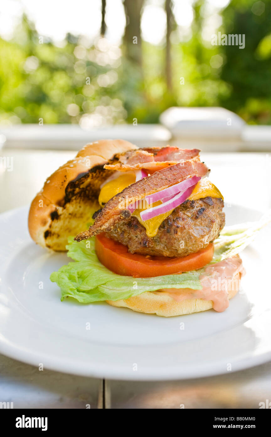 An American classic bacon cheeseburger fresh from the grill sits on a plate - Stock Image