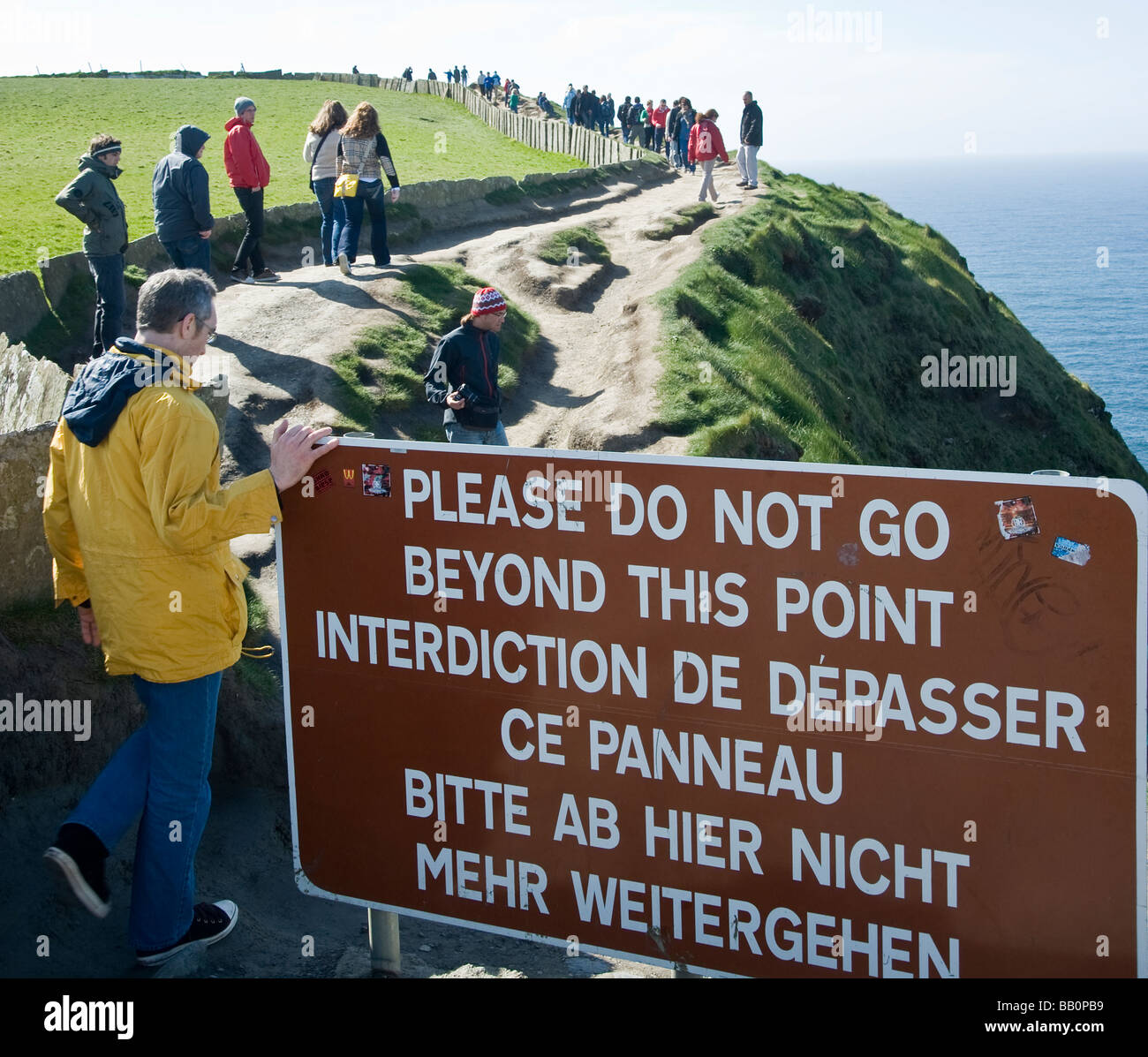 The sign may say Bitte ab jier nicht mehr weitergehen but no one seems to be able to read Cliffs Of Moher Ireland - Stock Image