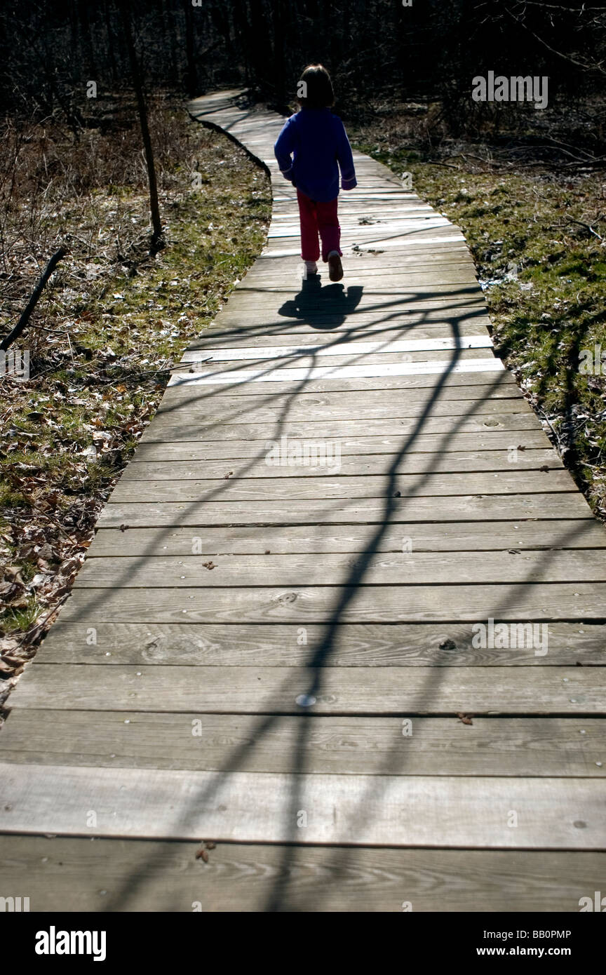 A young child explores the outdoors as she walks along a board walk. - Stock Image