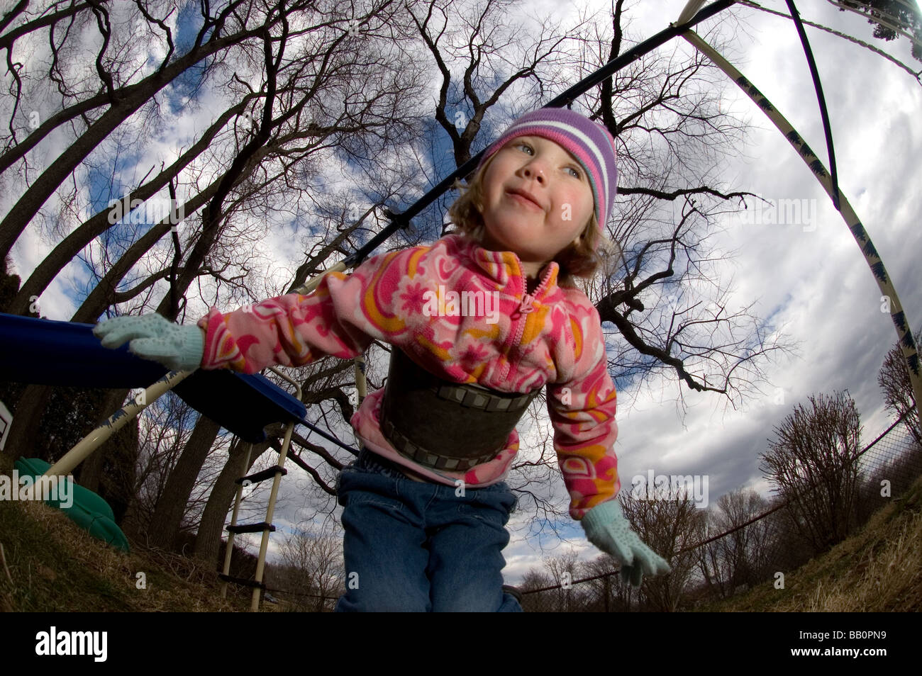 A young child pretend to fly on her swing during a cool day in her backyard - Stock Image