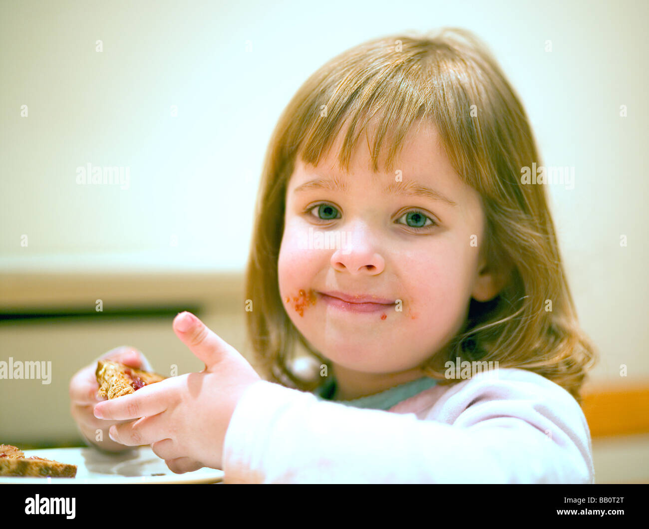 Three year old girl with peanut butter and jam toast - Stock Image