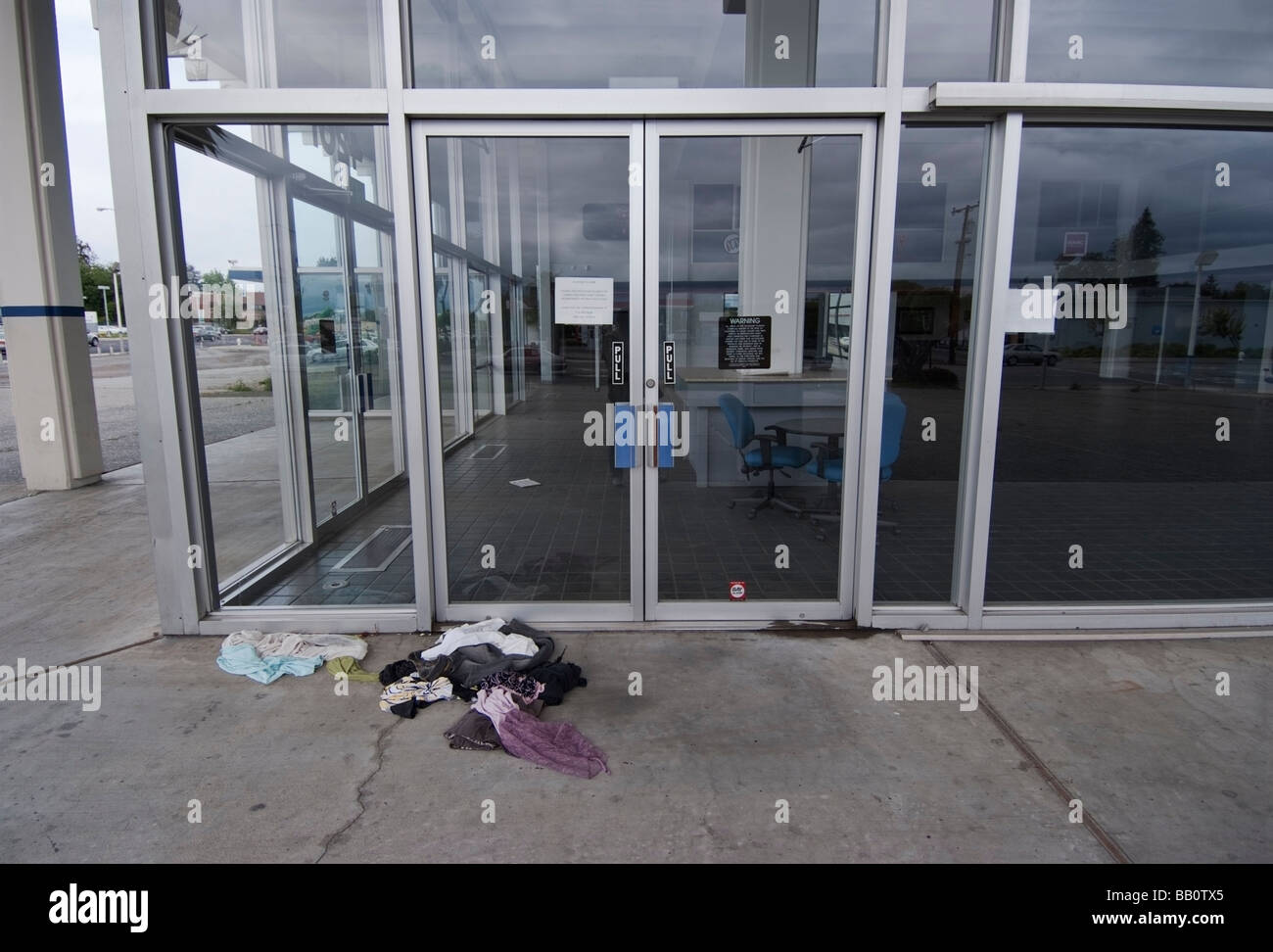 Abandoned clothing lying in front of the door to an empty showroom of a closed Buick Pontiac GMC Dealership in San - Stock Image