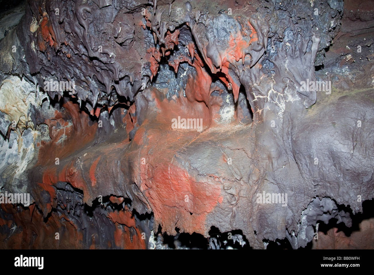Cooled lava with iron oxide deposit inside lava tube. Big Island Hawaii - Stock Image