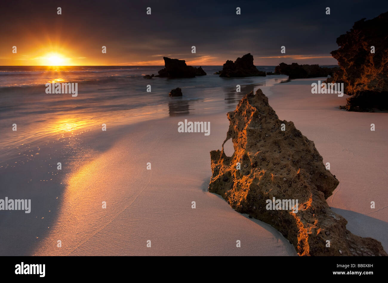 The sun dropping into the Indian Ocean at Trigg Beach in Perth, Western Australia - Stock Image